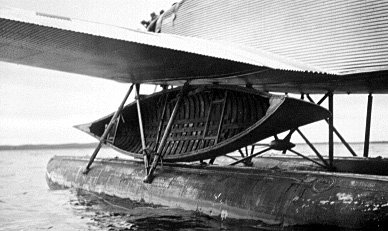 Number 9 Junkers aircraft on skis with two canoes strapped beneath its wing.